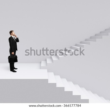 businessman standing on stairs on a gray background - stock photo