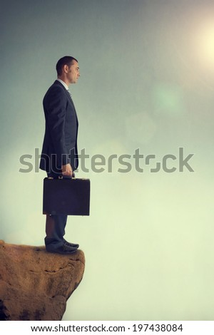 businessman standing on the edge of a cliff staring into the abyss - stock photo