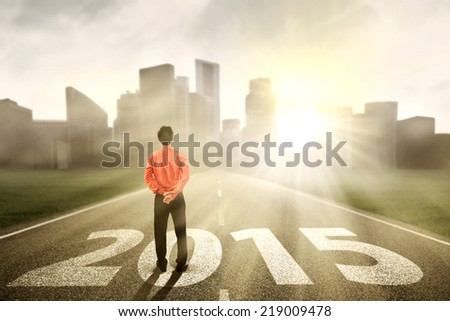 Businessman standing on the road and looking ahead in 2015 - stock photo
