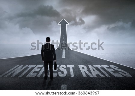 Businessman standing on the road turning into an arrow with interest rates words on it