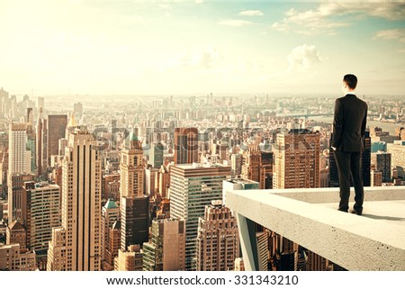Businessman standing on the roof of a skyscraper and looking over the city at sunset - stock photo