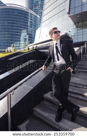 Businessman standing on the stairs of a business center and looks away.