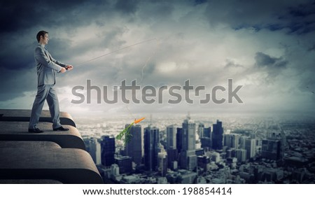 Businessman standing on top of building and fishing with rod