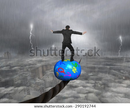 Businessman standing on top of colorful symbols ball, balancing on a wire, with heavy rain lightning overcast cityscape background. - stock photo