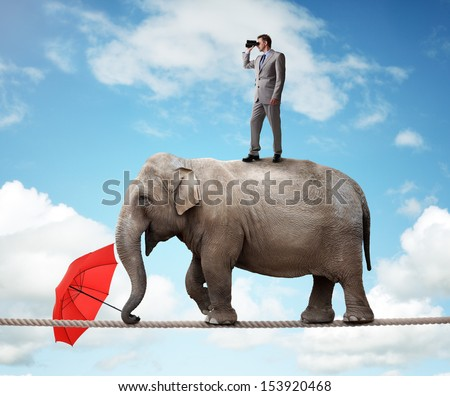 Businessman standing on top of elephant balancing on a tightrope looking through binoculars concept for business vision, conquering adversity or looking to the future - stock photo