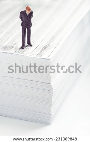 Businessman standing on top of office paper  - stock photo