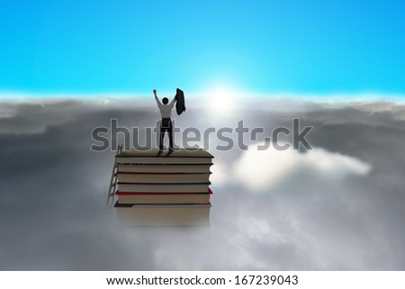 Businessman standing on top of stack of books with cloudy below and blue sky, sunlight