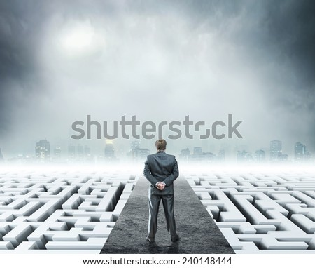 Businessman standing on white labyrinth - stock photo