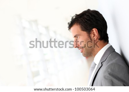 Businessman standing on white wall- profile view - stock photo