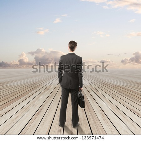businessman standing on wooden floor and looking  blue sky