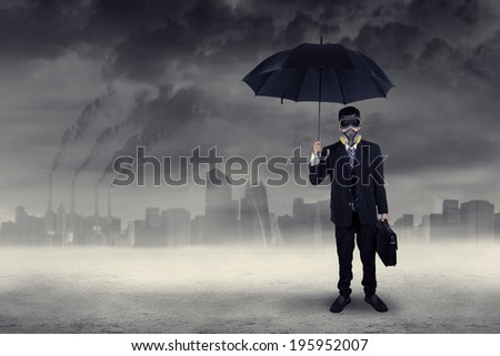 Businessman standing outdoors wearing a gas mask while holding an umbrella and briefcase