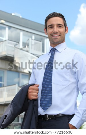 Businessman standing outside an office building - stock photo