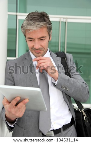 Businessman standing outside building with electronic tablet - stock photo