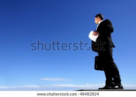 Businessman standing outside holding briefcase and contract