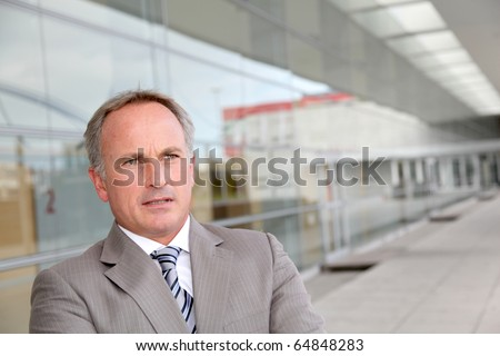 Businessman standing outside modern building - stock photo