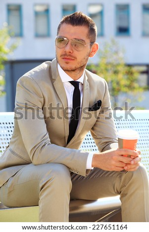Businessman standing outside the office with coffee  - stock photo