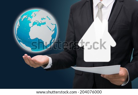 Businessman standing posture hand hold earth showing house isolated on dark background