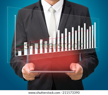Businessman standing posture hand hold graph on tablet isolated on blue background - stock photo