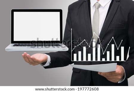 Businessman standing posture hand hold laptop showing graph isolated on gray background - stock photo