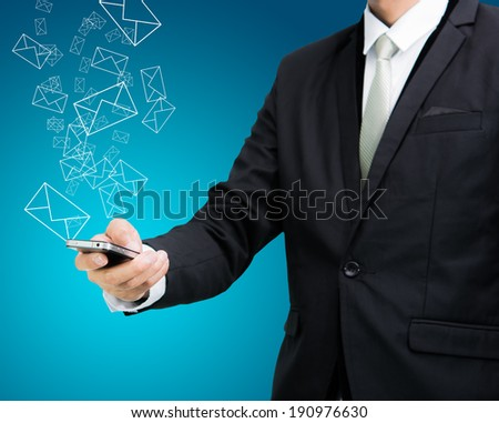 Businessman standing posture hand hold mobile phone send mail isolated on blue background - stock photo