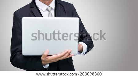 Businessman standing posture hand hold notebook laptop isolated on gray background - stock photo