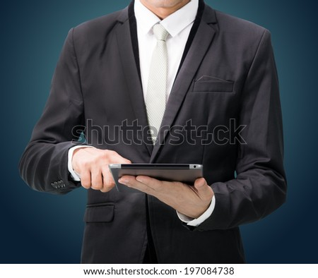 Businessman standing posture hand holding blank tablet isolated on dark background