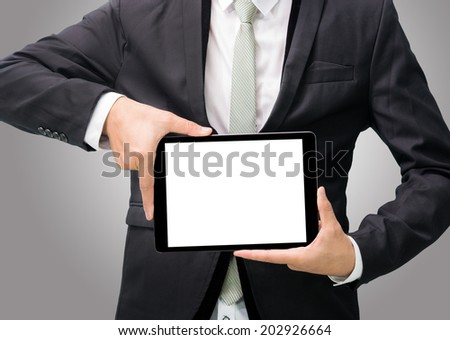 Businessman standing posture hand holding blank tablet on gray background - stock photo