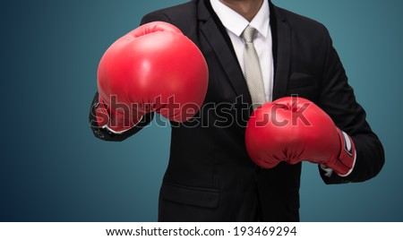 Businessman standing posture in boxing gloves isolated on over blue background - stock photo
