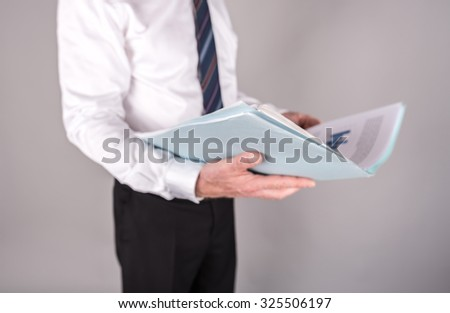 Businessman standing, reading a report, isolated on grey