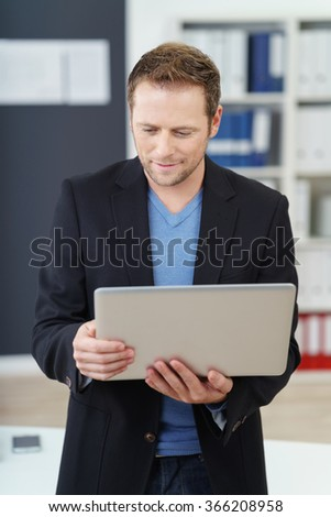 Businessman standing reading on his handheld laptop computer in the office with an engrossed expression and quiet smile - stock photo