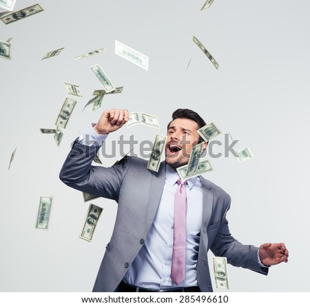 Businessman standing under money rain over gray background - stock photo