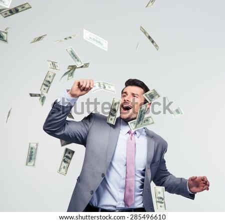 Businessman standing under money rain over gray background - stock photo