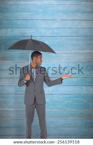 Businessman standing under umbrella against wooden planks