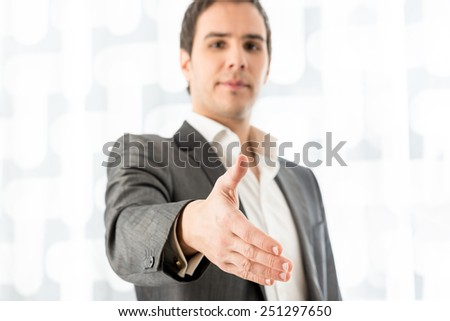Businessman standing up looking down offering his hand in a handshake as he concludes a deal with a partner or client. - stock photo