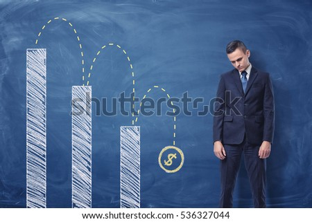 Businessman standing upset column diagram dollar stock photo businessman standing upset and a column diagram with a dollar sign falling down painted on the ccuart Images