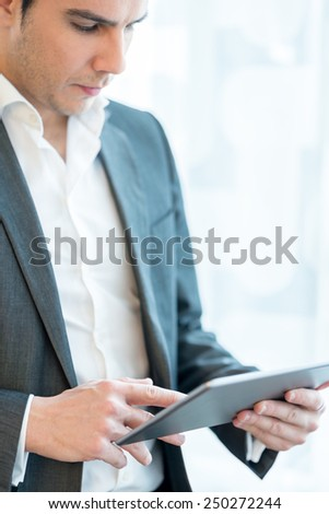 Businessman standing using a tablet computer over a high key background. Focus to the tablet. - stock photo