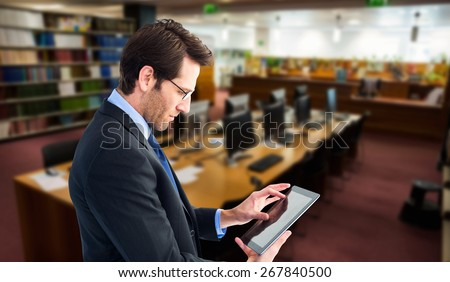 Businessman standing while using a tablet pc against computer desks in the library - stock photo
