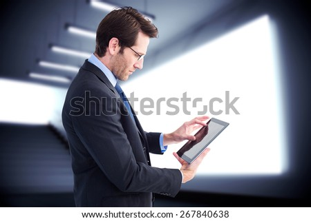 Businessman standing while using a tablet pc against grey room - stock photo