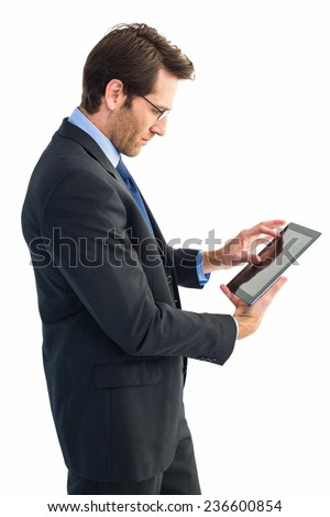Businessman standing while using a tablet pc on white background - stock photo
