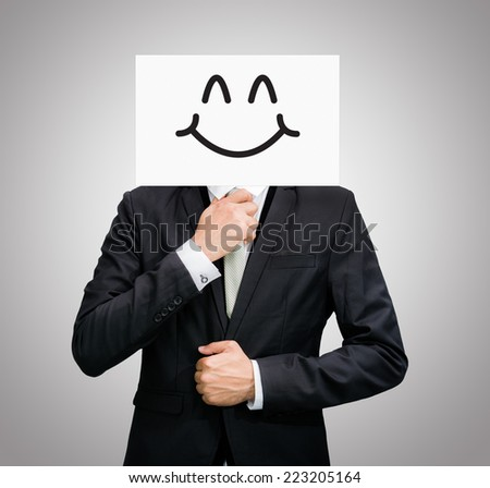Businessman standing white paper happy smile face holding front of head on gray background - stock photo