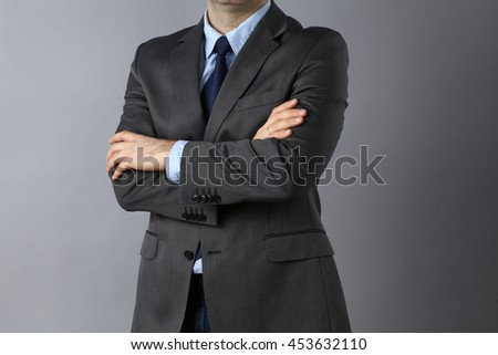 Businessman standing with arms crossed .
