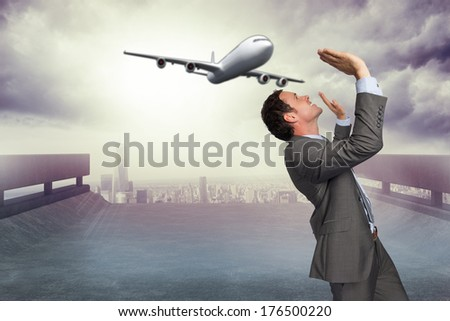 Businessman standing with arms pressing up against cityscape on the horizon