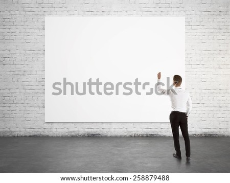 Businessman standing with back and writing on blank banner - stock photo