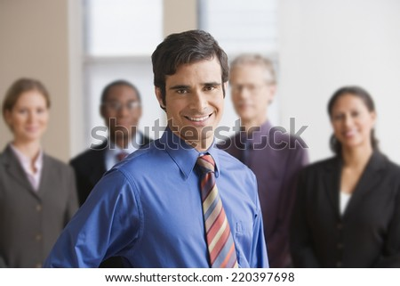 Businessman standing with coworkers in the background - stock photo