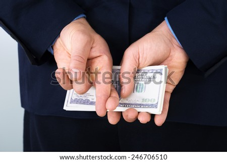 Businessman Standing With Crossed Finger And Holding Banknotes Behind His Back - stock photo