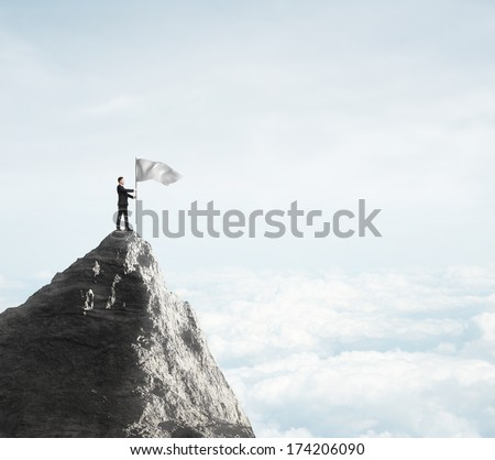 businessman standing  with flag on top of mountain