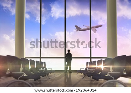 Businessman standing with hands on hips against airplane flying past departures lounge