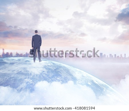 Businessman standing with his briefcase on a picture of the earth - stock photo