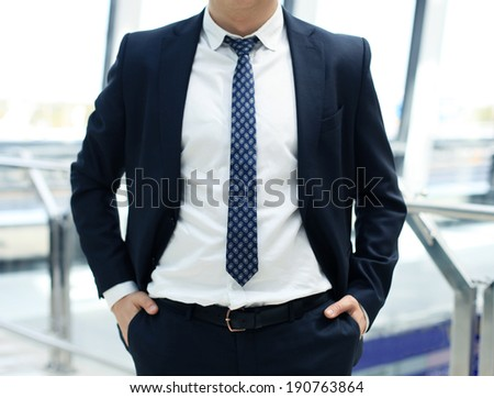 businessman standing with his hands in the pockets - stock photo