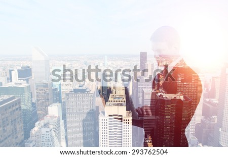 businessman standing with laptop in hand on city background - stock photo